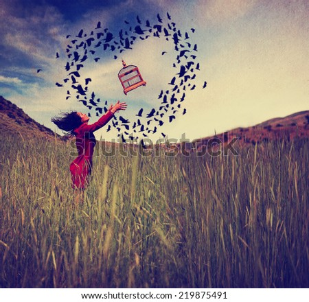 a girl in a field tossing a birdcage in the air with birds flying in the shape of a heart toned with a retro vintage instagram filter effect  - stock photo