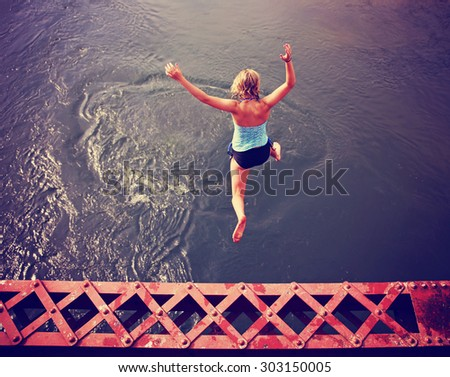 a girl jumping of an old train trestle bridge into a river toned during summer time toned with a retro vintage instagram filter effect - stock photo