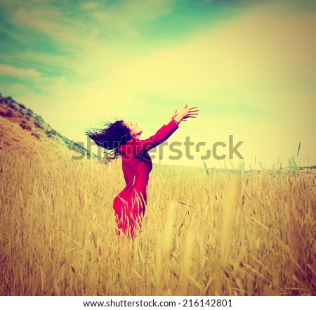 a girl walking in a field letting go of something toned with a retro vintage instagram filter effect - stock photo
