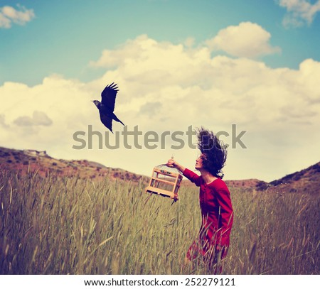 a girl walking in a wheat field on a warm summer day with a black bird toned with a retro vintage instagram filter - stock photo