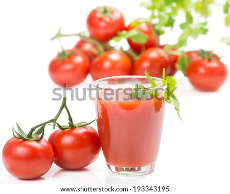A glass of tomato juice on the background of ripe tomatoes and green leaves isolated on white background.
