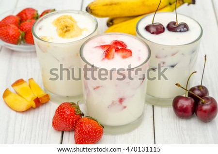 A glass of yogurt and fresh fruit on a white wooden background
