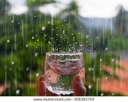 a glass to receive the water from the rain  concept of purity rain water for drinking - stock photo