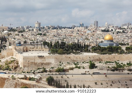 A gold dome and blue walls of a Muslim mosque and a modern city with skyscrapers. Majestic panorama of ancient Jerusalem.