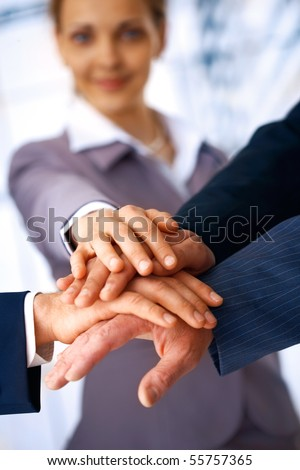A group of business people making a pile of hands with a woman at the background. - stock photo