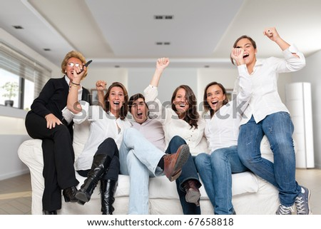 A group of family members sitting at home cheering - stock photo