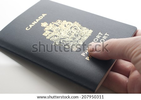 A hand holding a Canadian Passports - stock photo