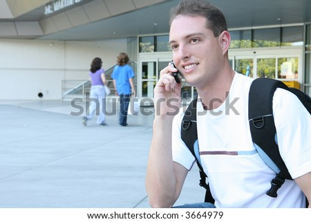 A handsome male college student smiling on his cell phone