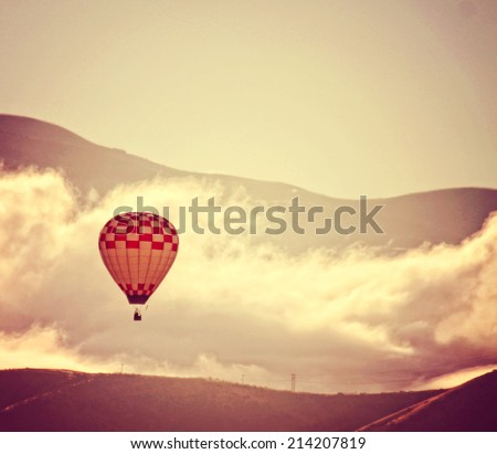a hot air balloon in the sky in front of clouds toned with a retro vintage instagram filter effect - stock photo
