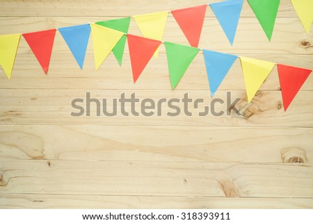 a line of colourful party flags on wooden background with space for text - stock photo