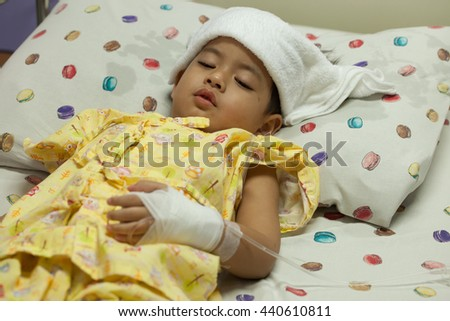a little Boy attaching intravenous tube to patient's hand in hospital bed, thermometer boy hospitalized patients, towel to hi fever, Select Focus - stock photo