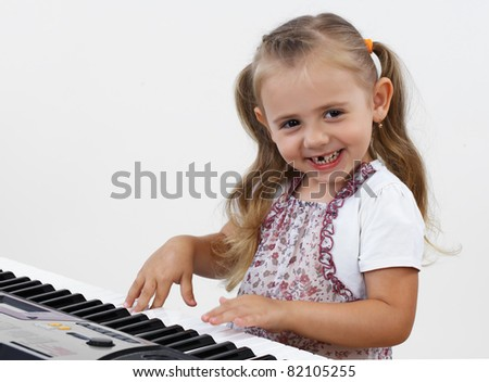 A little girl plays on a musical keyboard