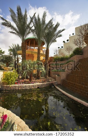 A magnificent fountain and a tower for descent in pool in a court yard of fine hotel - stock photo