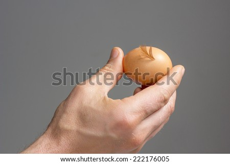 A male hand with the hen egg and feather./	Hens egg with a signature