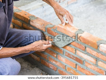 a man hands installing red brick with trowel putty knife  - stock photo