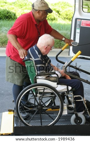 A man helps another into a wheelchair equipped van. - stock photo