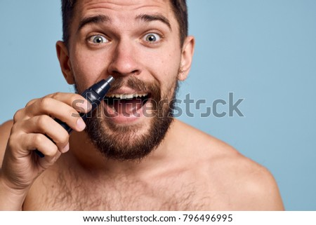 a man joyful with a trimmer on a blue background, shave