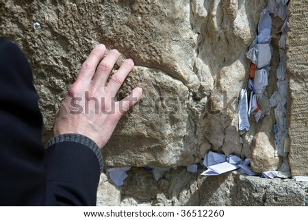 A man praying at the wailing wall - focus on hand - stock photo