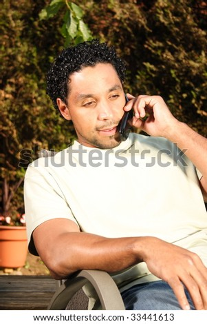 A man sitting on his deck outside talking on a cell phone
