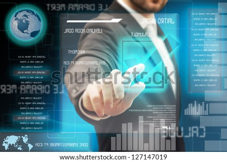 A man touching a button on a futuristic touchscreen interface - stock photo
