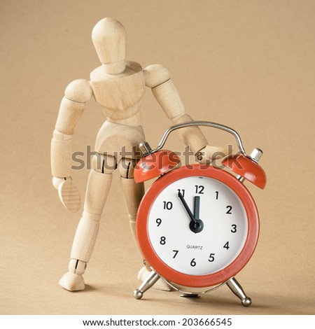 A mannequin and clock are isolated to represent time management. - stock photo