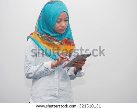 A muslim lady using a tablet computer. - stock photo