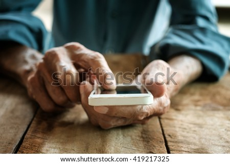 a old man hand using mobile smart phone on the wood table - stock photo