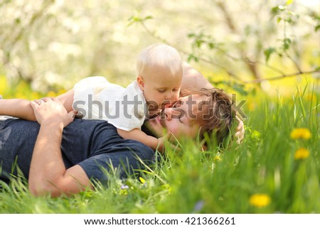A one year old baby girl is holding her father's face and looking lovingly at him as they hug while relaxing in the meadow on a spring day.