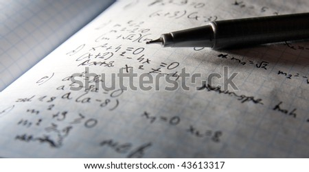 A pen with page of maths notebook in background- dramatic lightening - stock photo