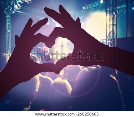a person making a heart shape with their hands over a crowd of people at a concert toned with a retro vintage instagram filter effect  - stock photo
