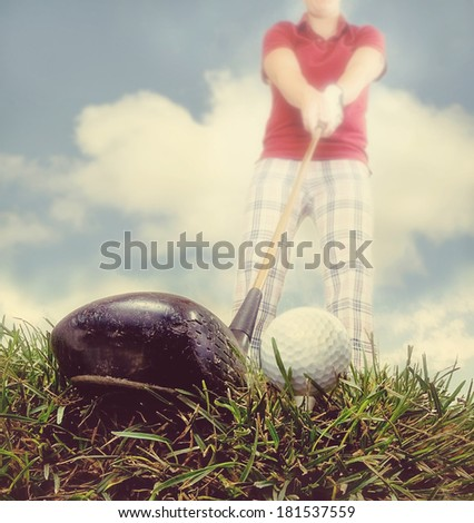 a person playing golf as seen through a wide angle lens done with an instagram like filter - stock photo
