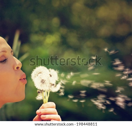 a pretty woman blowing on dandelion weed flowers