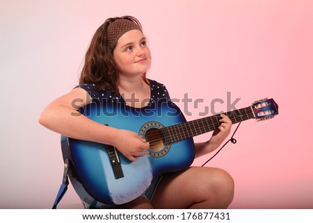 A pretty young brunette girl is playing a blue guitar in studio.