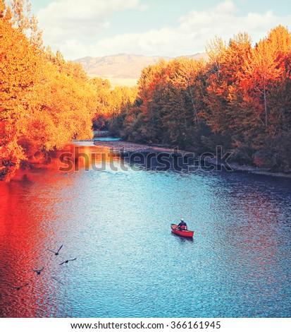 a river flowing in autumn with a kayaker paddling in the water toned with a retro vintage instagram filter effect app or action  - stock photo