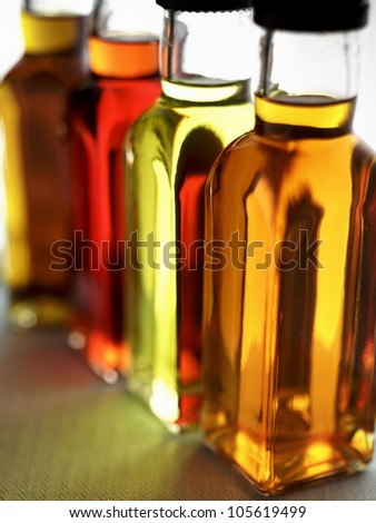 a row of colored oil bottles on a green herringbone fabric in portrait - stock photo