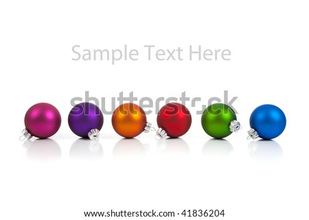 A row of Multi-colored Christmas ornaments/baubles including pink, red, orange, blue, purple and green on a white background with copy space