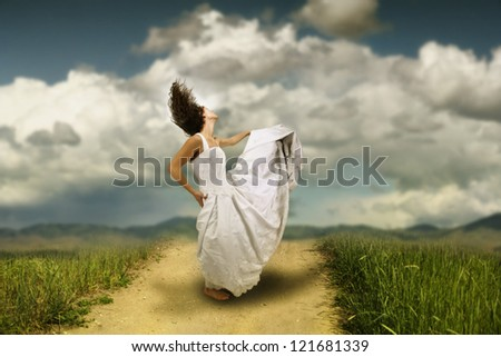 a runaway bride dancing on a path in a meadow - stock photo