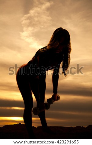 A silhouette of a woman working out with weights, working out her hamstrings. - stock photo