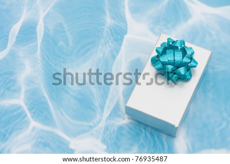 A silver present with bow on aqua background, holiday giving - stock photo