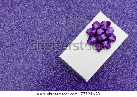 A silver present with bow on purple background, holiday giving - stock photo