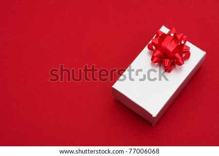 A silver present with bow on red background, holiday giving - stock photo