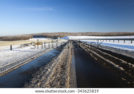 a small country road passes in a field in winter. covered with snow