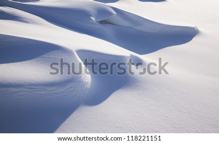 a snowdrift formed after a snow storm and a strong wind - stock photo