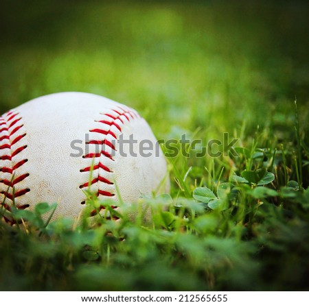 a square photo of a baseball in a grass background toned with a vintage retro instagram filter  effect - stock photo