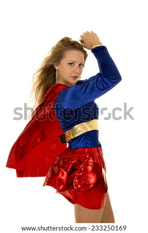 A super hero woman with her cape flying and flexing her arms. - stock photo