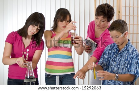 a teacher working with some kids on a chemistry project. - stock photo