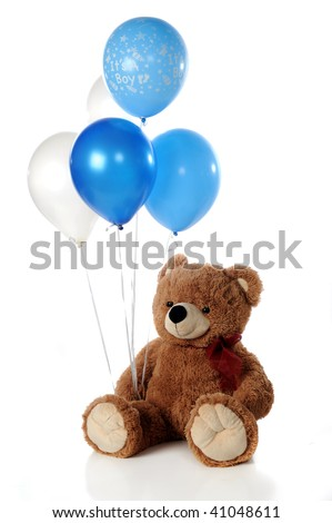 """A Teddy bear holding five blue and white helium balloon.  One proclaims, """"It's a boy.""""  Isolated on white. - stock photo"""