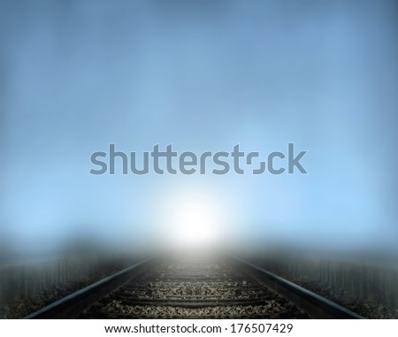 a train coming down tracks at night in the fog  - stock photo