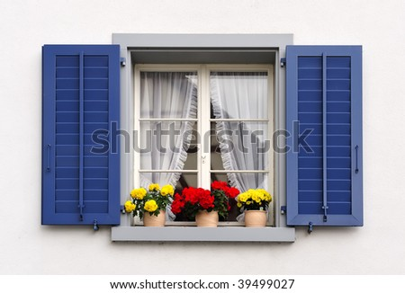 a typical switzerland window with louvered shuters and square paned windows with flowers in hanging flower pots