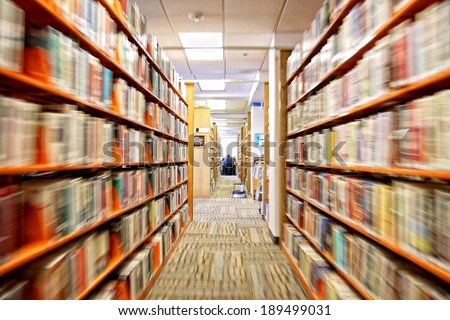 a view of an aisle in a public library  - stock photo
